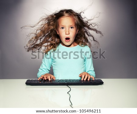 Surprised little girl with computer keyboard. Child looking at computer - stock photo