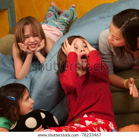 Surprised little girl with hands on head with friends at a sleepover - stock photo
