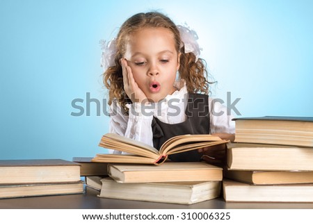 Surprised Little Schoolgirl Sits At Table With Books On Blue Background - stock photo