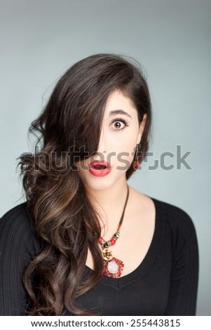 Surprised look hispanic girl on grey background - stock photo