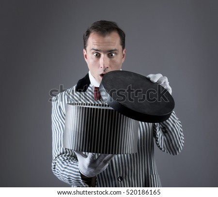 Surprised magician looking into a box