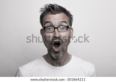 Surprised man Face shot of an enthusiastic man with glasses and stubbly beard opening mouth due to a big unexpected surprise