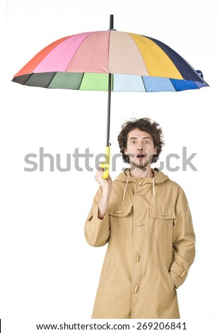 Surprised man in brown vintage raincoat holding colorful umbrella. - stock photo