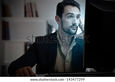 Surprised man looking at a computer screen, in a dark room - stock photo