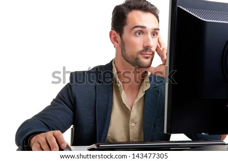 Surprised man looking at a computer screen, thinking about the job at hand - stock photo