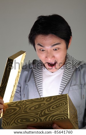 Surprised man opening a glowing box - stock photo