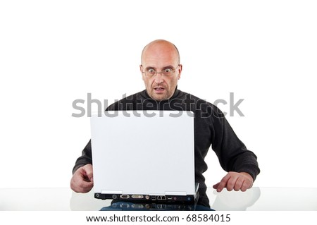 Surprised man sits at the desk with a laptop, isolated on white - stock photo