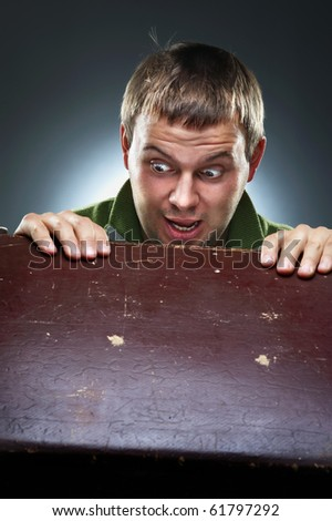 Surprised man staring at the open chest - stock photo