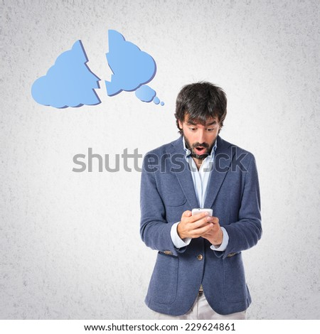 Surprised man talking to mobile over grey background - stock photo
