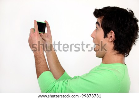 Surprised man watching his cellphone - stock photo