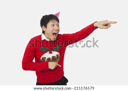 Surprised man wearing Christmas sweater while pointing over white background - stock photo
