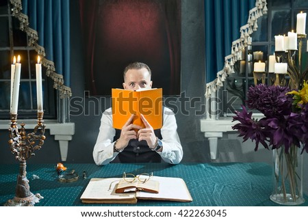 Surprised man with a book in hands at the table in his study
