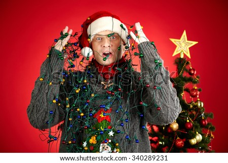 Surprised man with garland all over him looking at camera - stock photo