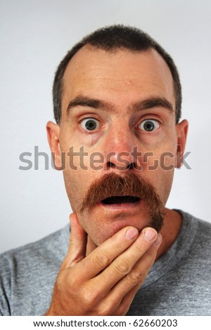 surprised man with uneven mustache trimmed more on one side than the other - stock photo