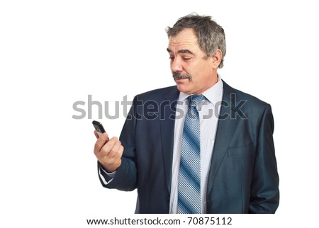Surprised mature business man holding a cellphone and reading isolated on white background