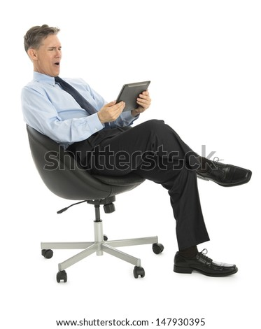 Surprised mature businessman looking at tablet computer while sitting on office chair against white background - stock photo
