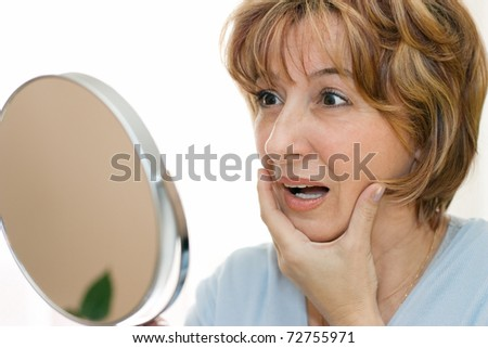 Surprised mature woman looking at her face in the mirror. - stock photo