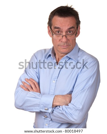 Surprised Middle Age Man in Blue Shirt with Arms Folded Looking Over Glasses - stock photo