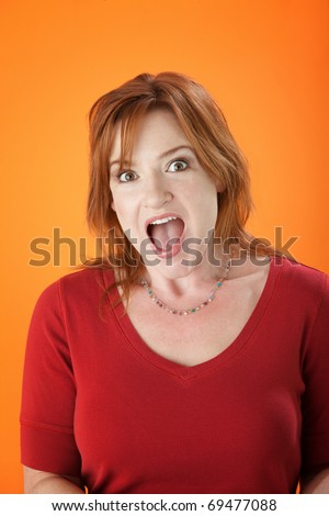 Surprised middle-aged woman with raised eyebrows and open mouth - stock photo
