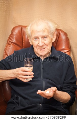 surprised old man with a questioning look holding a glass of water and a mix of pills - stock photo