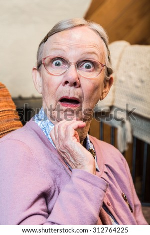 Surprised old matron woman looking at camera - stock photo