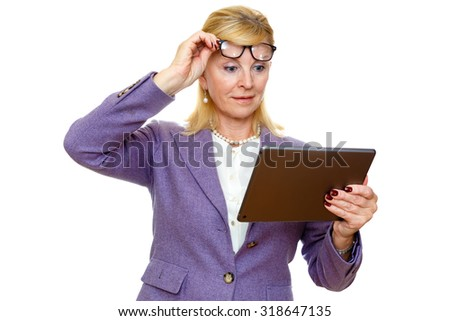 Surprised old senior business woman 60-65 years in glasses and suit, using digital tablet pc computer reading ebook. Isolated on white background - stock photo