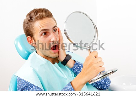 Surprised patient looking in the mirror after dental treatment - stock photo