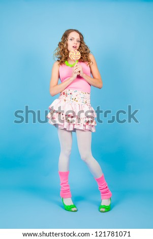 Surprised pin-up woman with colorful lollipop on the blue background - stock photo