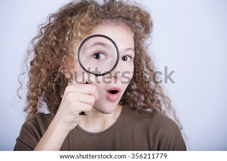 Surprised portrait of cute little girl looking through  magnifying glass.Curious Smiling little girl looking through magnifying glass over white background.