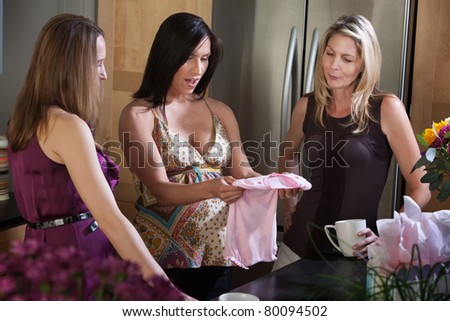 Surprised pregnant lady with baby clothes gift from friends - stock photo