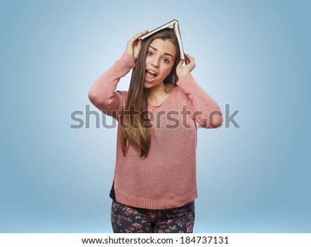 surprised pretty girl with book on head - stock photo
