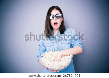 Surprised pretty woman in cinema glasses eating popcorn over gray background. Looking at camera - stock photo