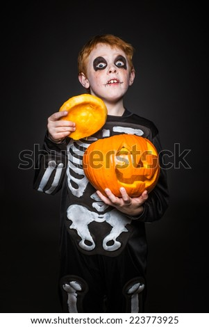 Surprised red haired child in skeleton costume holding a orange pumpkin. Halloween. Studio portrait over black background - stock photo