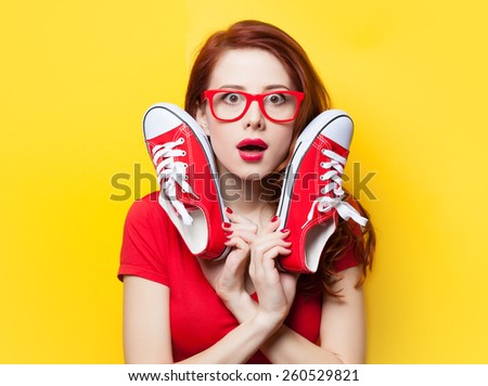 Surprised redhead girl in red dress with gumshoes on yellow background. - stock photo