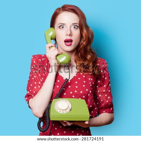 Surprised redhead girl in red polka dot dress with green dial phone on blue background. - stock photo