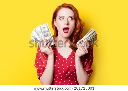 Surprised redhead girl in red polka dot dress with money on yellow background. - stock photo
