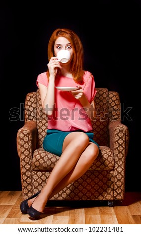 Surprised redhead girl with cup of coffee. 70s - stock photo