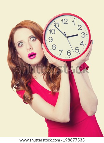 Surprised redhead girl with huge alarm clock on light background. - stock photo