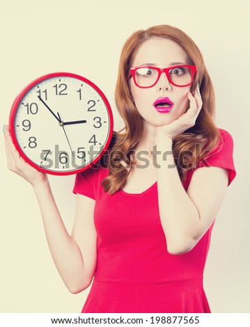 Surprised redhead girl with huge alarm clock on light background.