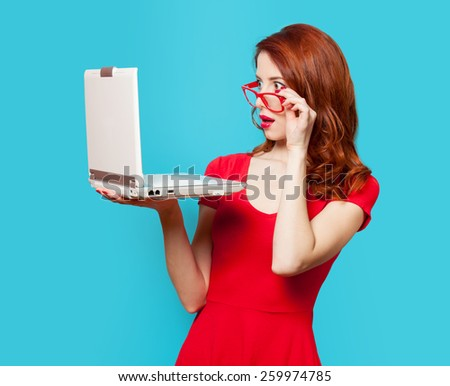 Surprised redhead girl with laptop on blue background - stock photo