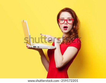 Surprised redhead girl with laptop on yellow background - stock photo