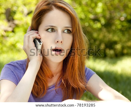 Surprised redhead girl with mobile phone at the park in summer time. - stock photo