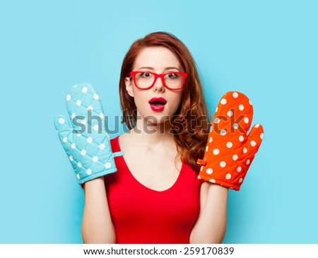 Surprised redhead girl with oven gloves on blue background - stock photo