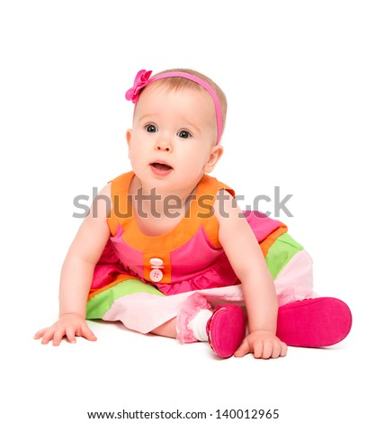surprised, sad little baby girl in bright multicolored festive dress isolated on a white background - stock photo