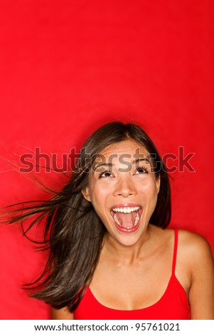 surprised screaming woman looking up at copy space on red background. Beautiful young shocked mixed race Caucasian / Asian female model amazed. - stock photo