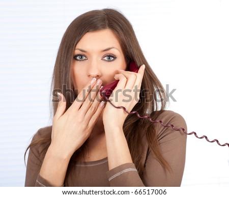 surprised secretary woman speaking on the phone - stock photo