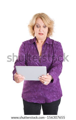 Surprised senior woman standing with tablet computer over white background - stock photo