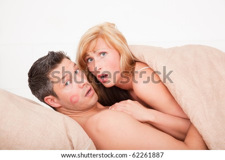 Surprised sex couple lying in bed with lipstick kiss - stock photo