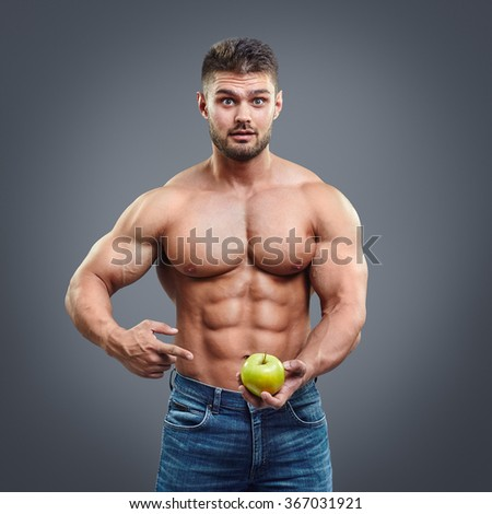 Surprised shirtless muscular man pointing to fresh green apple. Healthy food and vitamins abstract concept. Bodybuilder sport nutrition.