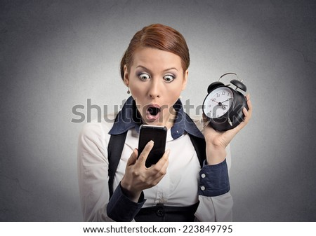 Surprised shocked business woman with alarm clock looking at smart phone with funny  face expression late for meeting isolated grey wall background. Human face expression, emotions, feelings, reaction - stock photo